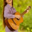 Smiling teenage girl playing guitar — Stock Photo