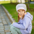 Girl-preschooler sitting on stone curb - Stock Photo