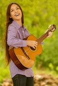 Lächelnd teenager-mädchen-gitarre spielen — Stockfoto