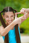 Smiling teenage girl pictures of virtual camera — Stock Photo