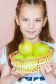 Girl-preschooler holding wicker basket of apples — Stock Photo