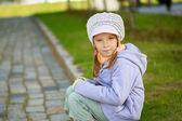 Girl-preschooler sitting on stone curb — Stock Photo