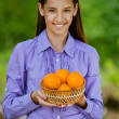 Royalty-Free Stock Photo: Smiling teenage girl holding basket of oranges