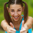 Smiling teenage girl picks up big thumbs up — ストック写真