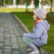 Girl-preschooler sitting on stone curb — Stock Photo
