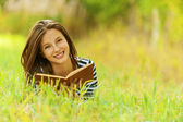 Smiling woman lying on grass reading book — Stock Photo