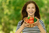 Woman holding basket of tomatoes and cucumbers — Stock Photo