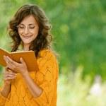 Woman in orange sweater reading book — Stock Photo