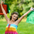 Woman happily holds up with shopping bags — Stock Photo