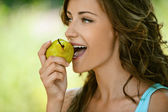Woman close-up in blue shirt pear bites — Stock Photo