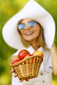 Woman wiht wicker basket holds red apples — Stock Photo