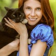 Young woman with black cat — Stock Photo