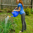 Stock Photo: Young woman bow waters from watering