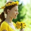 Young woman in with bouquet of dandelions - Stock Photo