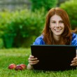 Stock Photo: Young woman lying on grass with laptop