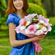 Young woman with bouquet of flowers - Stock Photo