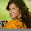 Woman is typing with stylus on device - Stock Photo