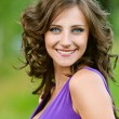 Young woman in a purple dress happily smiling - Stock Photo