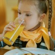 Royalty-Free Stock Photo: Girl-preschooler drinking orange juice