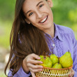 Smiling teenage girl holding basket of pears — Stock Photo
