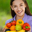 Teenage girl holding banana, peppers, pears and oranges — Stock Photo #12408295