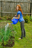 Young woman bow waters from watering — Stock Photo