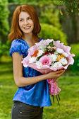 Młoda kobieta z bukietem kwiatów — Zdjęcie stockowe