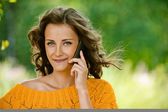 Woman in orange sweater talking on cell phone — Stock Photo