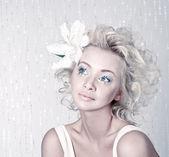 Hermosa mujer joven con maquillaje original y flor — Foto de Stock