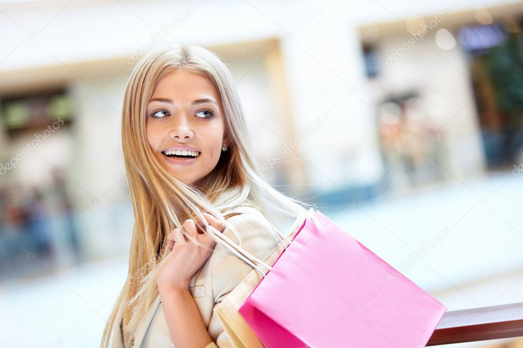 Smiling girl with shopping bags in shop — Stock Photo #10953746