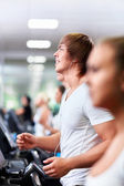 Smiling on treadmills — Stock Photo