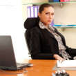 Business woman sitting in the office in front of the laptop — Stock Photo #10835209