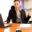 Business woman sitting in the office in front of the laptop - Stock Photo