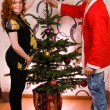 Happy couple decorating Christmas tree with baubles — 图库照片