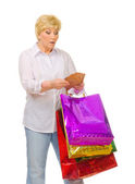 Senior woman with wallet and bags — Stock Photo