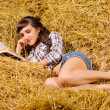 Royalty-Free Stock Photo: Woman reading book on haystack