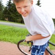 Smiling boy riding bike on bicycle path — Stock Photo