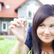 Woman holding keys with house background — Stock Photo