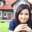 Woman holding keys with house in background — Stock Photo #11804542