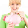 Girl putting euro in pink piggy bank — Stock Photo #11049764