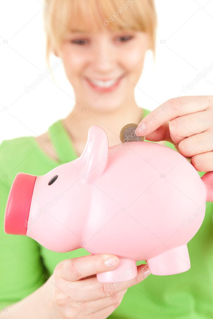 Smiling young woman putting euro coin into pink piggy bank, focus on foreground, white background   #11049749