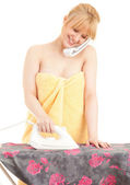 Woman with phone ironing clothes — Stockfoto