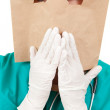 Ashamed doctor with bag on head - Stock Photo