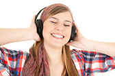 Happy girl listening music in headphones — Stock Photo