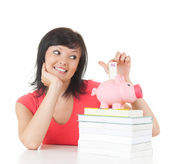 Woman putting euro in piggy bank — Stock Photo