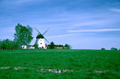 White windmill on the green farm field — Stock Photo