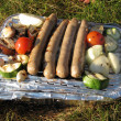 Single-use grill with vegetables and sausages - Stock Photo