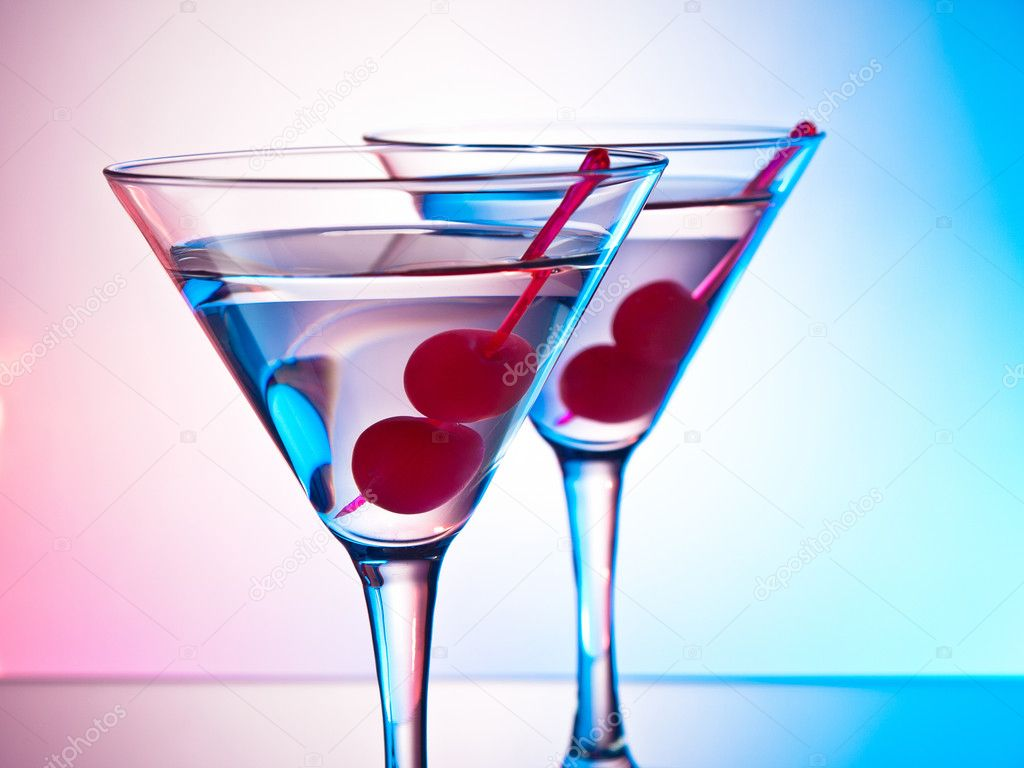 Two glasses of martini with red cherries on a moxed color background — Stock Photo #10968344
