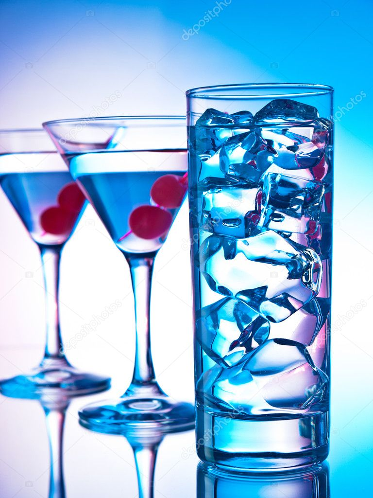 Two glasses of martini with red cherries and a glass of clear cocktail — Stock Photo #10968399