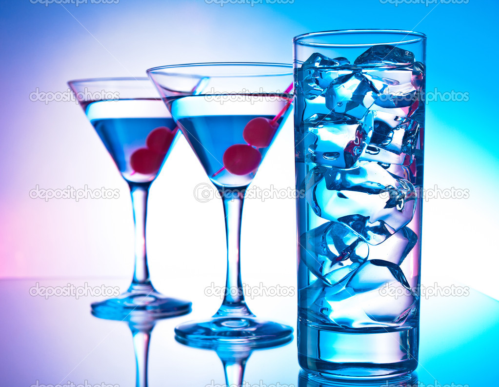 Two glasses of martini with red cherries and a glass of clear cocktail  Stock Photo #10968405